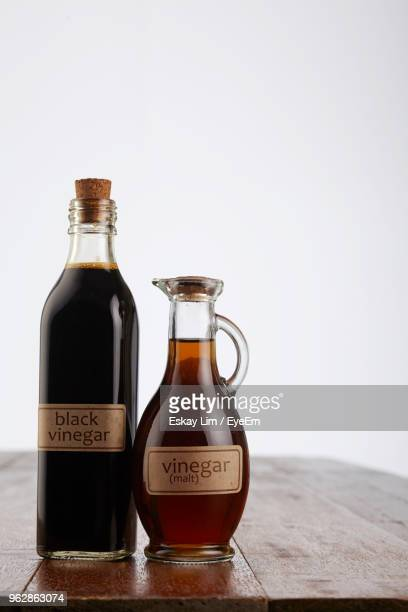 Close-Up Of Vinegar In Bottles On Table Against White Background
