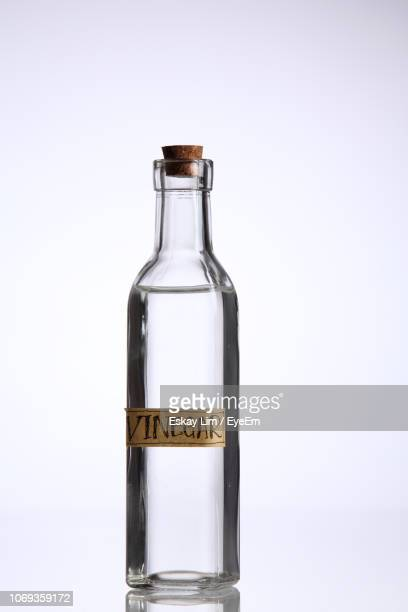 Close-Up Of Vinegar Text On Glass Bottle Against White Background