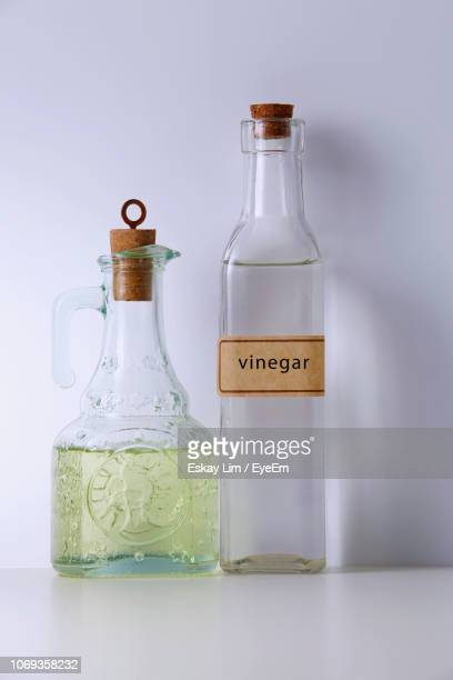 Close-Up Of Vinegar With Cooking Oil On Table Against White Background