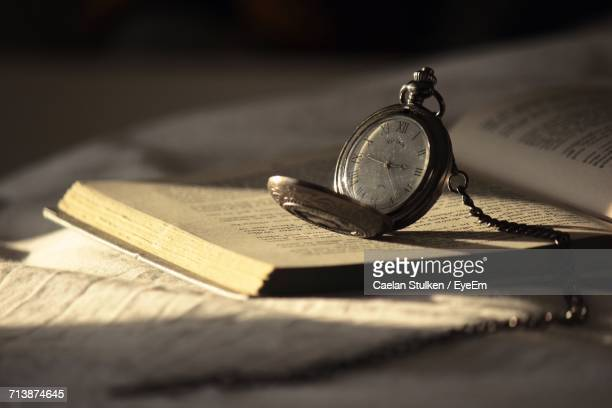 Close-Up Of Vintage Pocket Watch On Book