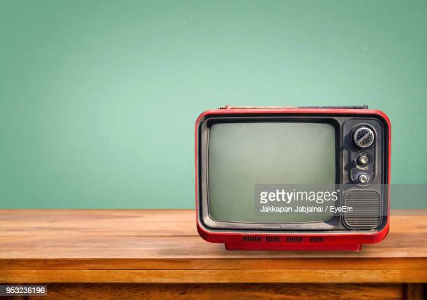close-up of vintage television set on table against green wall - television industry stock photos and pictures