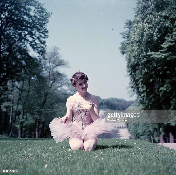 Close-up Of Violette Verdy. Dans un parc, lors d'une séance de portraits, la danseuse Violette VERDY souriante, en tutu, agenouillée dans l'herbe.