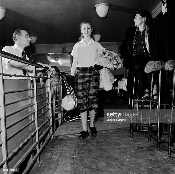 Close-up Of Violette Verdy. Dans une salle de restaurant, portrait de la danseuse Violette VERDY tenant un sac, un manteau au bras.