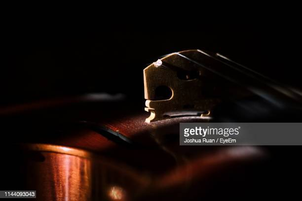 close-up of violin against black background - musical instrument string stock pictures, royalty-free photos & images