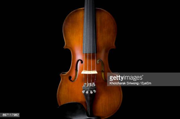 close-up of violin against black background - stringed instrument stock pictures, royalty-free photos & images