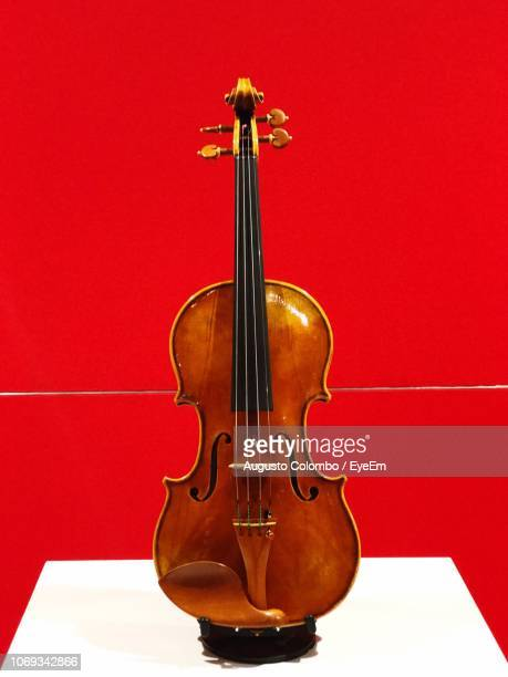 close-up of violin against red wall - cremona stock pictures, royalty-free photos & images