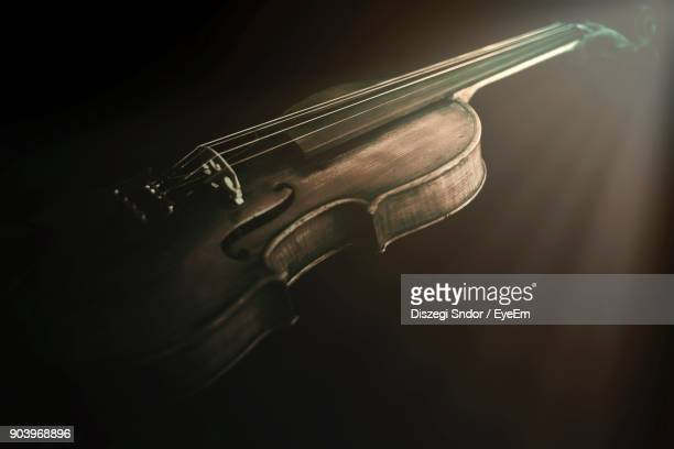 close-up of violin over black background - string instrument stock photos and pictures