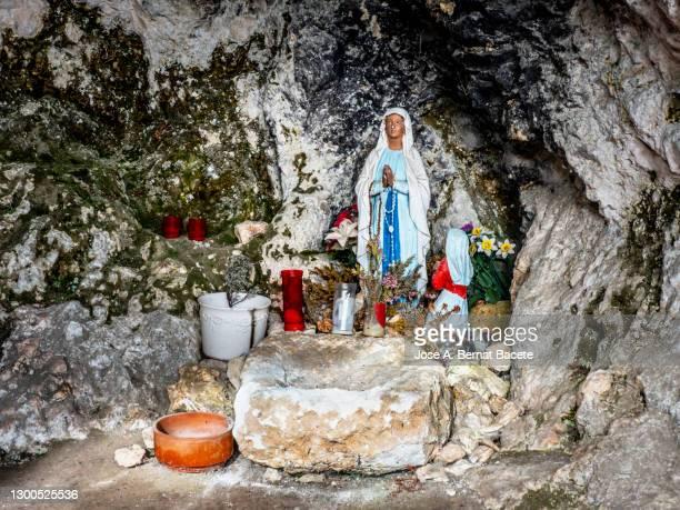 close-up of virgin mary figurine inside a small cave in the field. - madonna del rosario foto e immagini stock