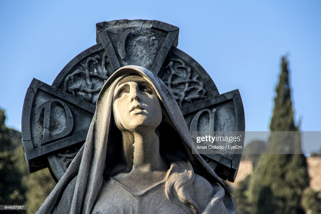 Close-Up Of Virgin Mary Statue Against Celtic Cross At Cemetery : Stock Photo