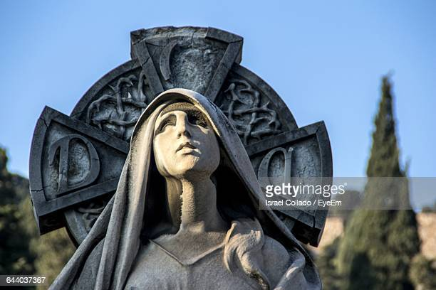 Close-Up Of Virgin Mary Statue Against Celtic Cross At Cemetery