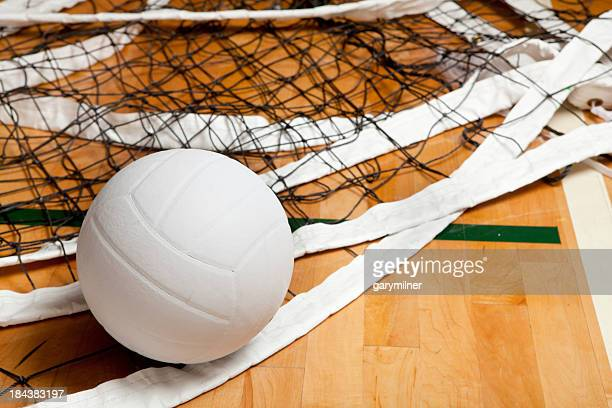 Close-up of volleyball in net on gym floor