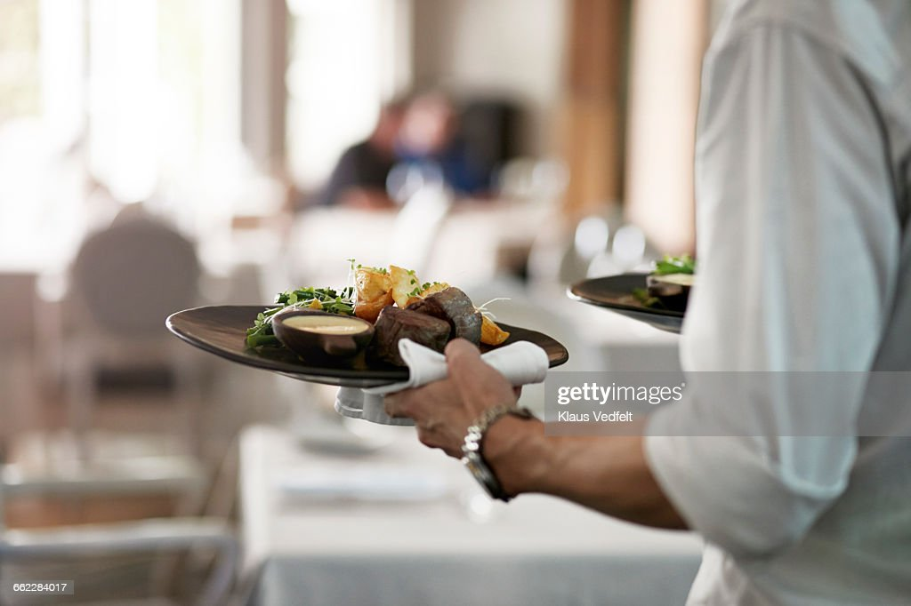 Close-up of waiter walkiing with dishes : Stock-Foto
