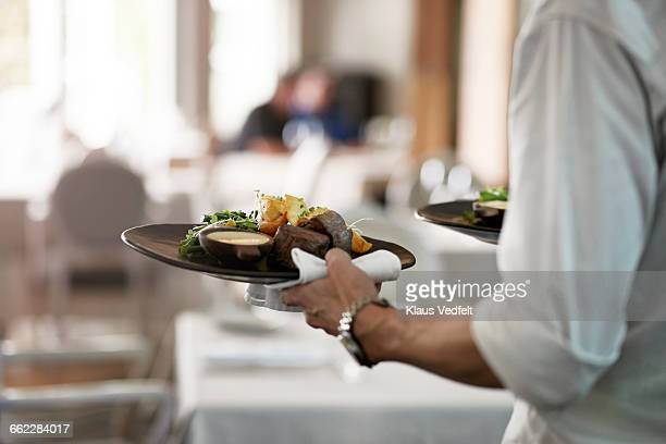 close-up of waiter walkiing with dishes - restaurant stock photos and pictures