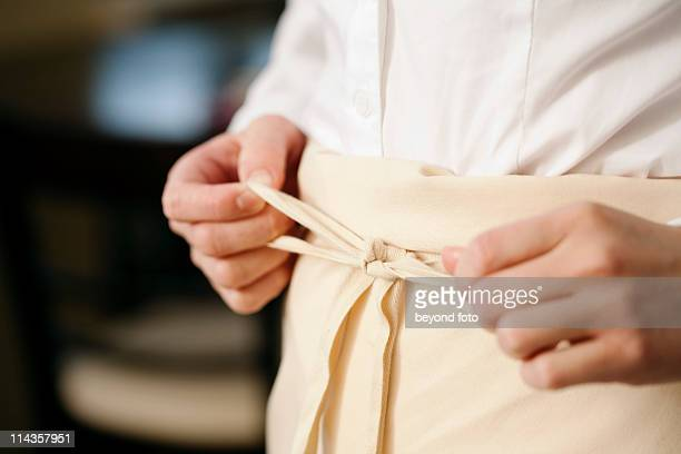 close-up of waitress in restaurant tying apron