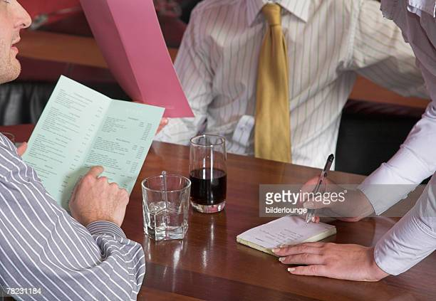 close-up of waitress standing at table writing down order in restaurant