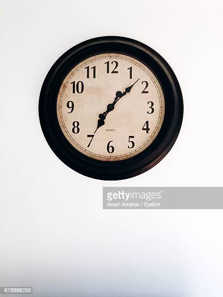 close-up of wall clock against white background - wall clock stock photos and pictures