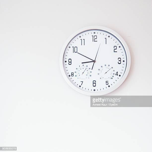close-up of wall clock over white background - wall clock stock photos and pictures