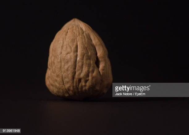 close-up of walnut against black background - nutshell stock photos and pictures