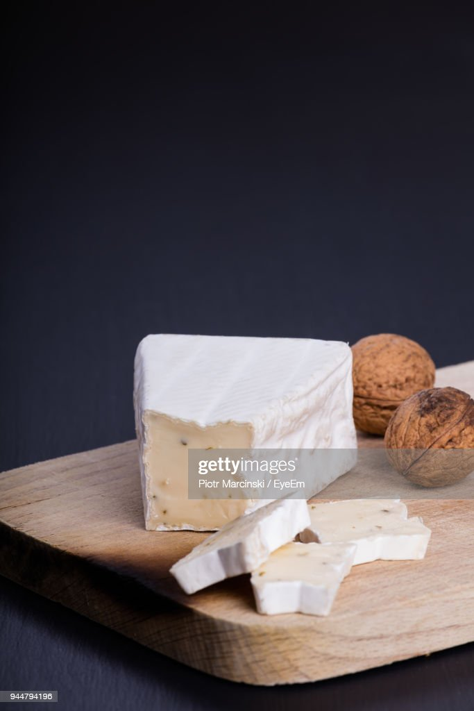 Close-Up Of Walnuts And Cheese On Cutting Board Against Black Background : Stock Photo