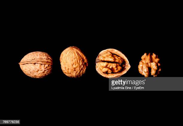 close-up of walnuts arranged over black background - nutshell stock photos and pictures