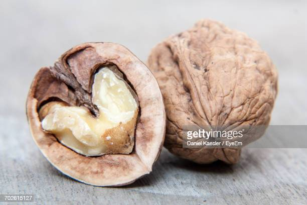 close-up of walnuts on wooden table - nutshell stock photos and pictures