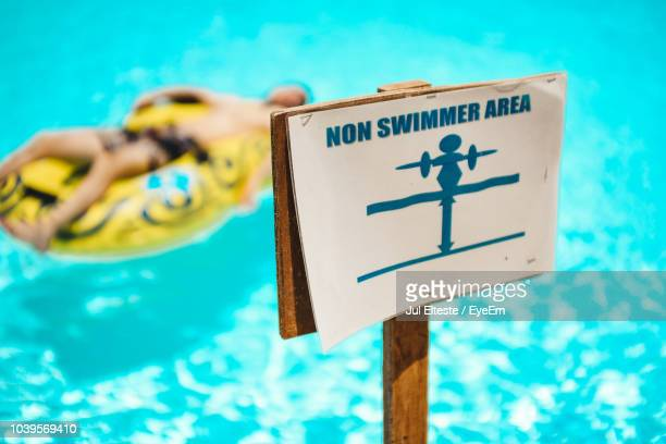 Close-Up Of Warning Sign Against Swimming Pool