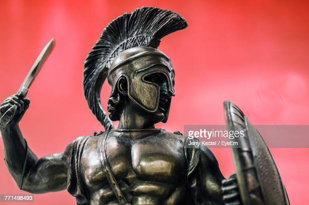 Close-Up Of Warrior Statue Against Red Wall