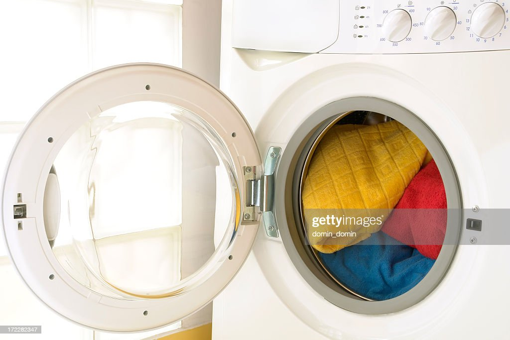 Close-up of washing machine, opened door, laundry inside, three towels : Stock Photo