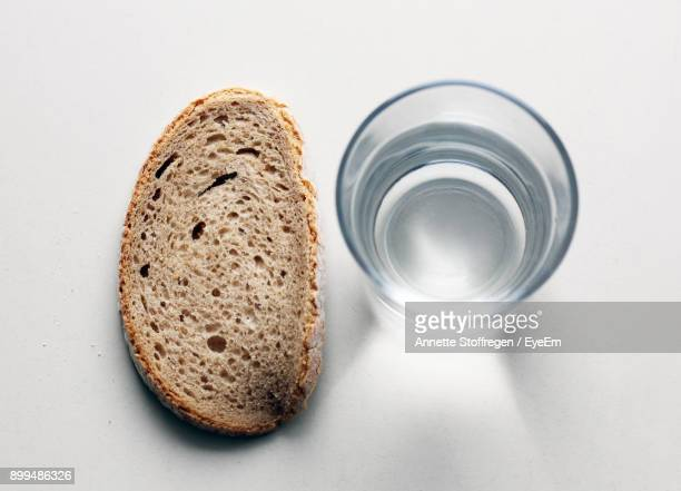 Close-Up Of Water And Bread On White Background