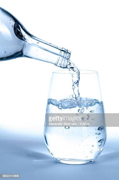 close-up of water being poured into glass against white background - glass of water stock pictures, royalty-free photos & images