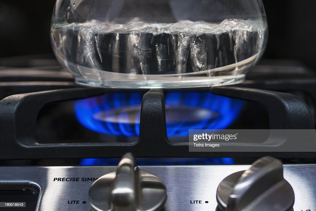 Close-up of water boiling on gas burner : Stock Photo