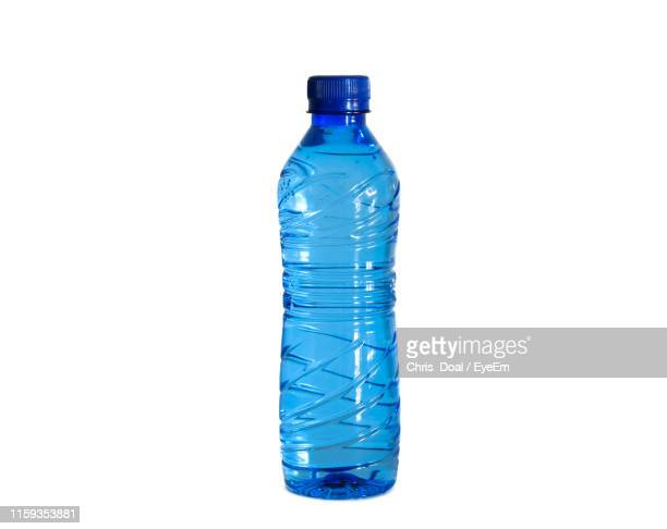 close-up of water bottle against white background - fles stockfoto's en -beelden