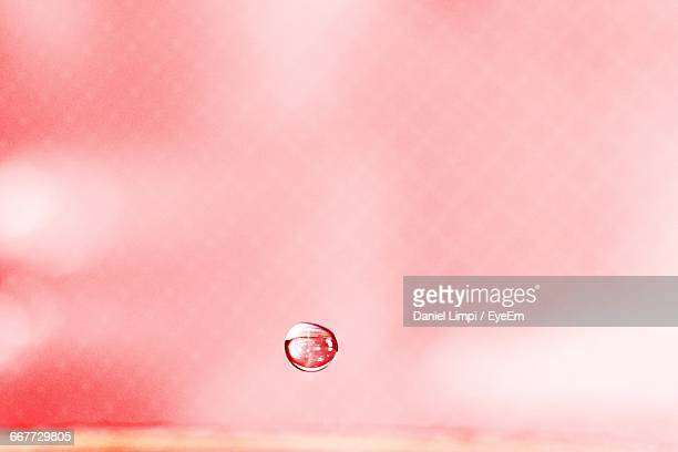 Close-Up Of Water Drop Against Pink Background