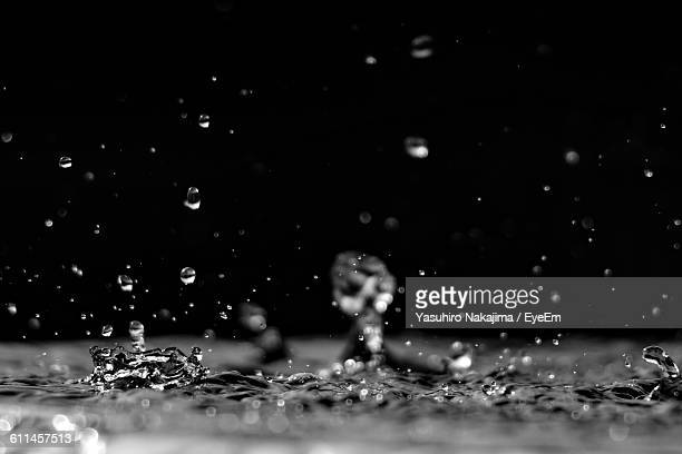 Close-Up Of Water Drops Splashing On Floor Against Black Background