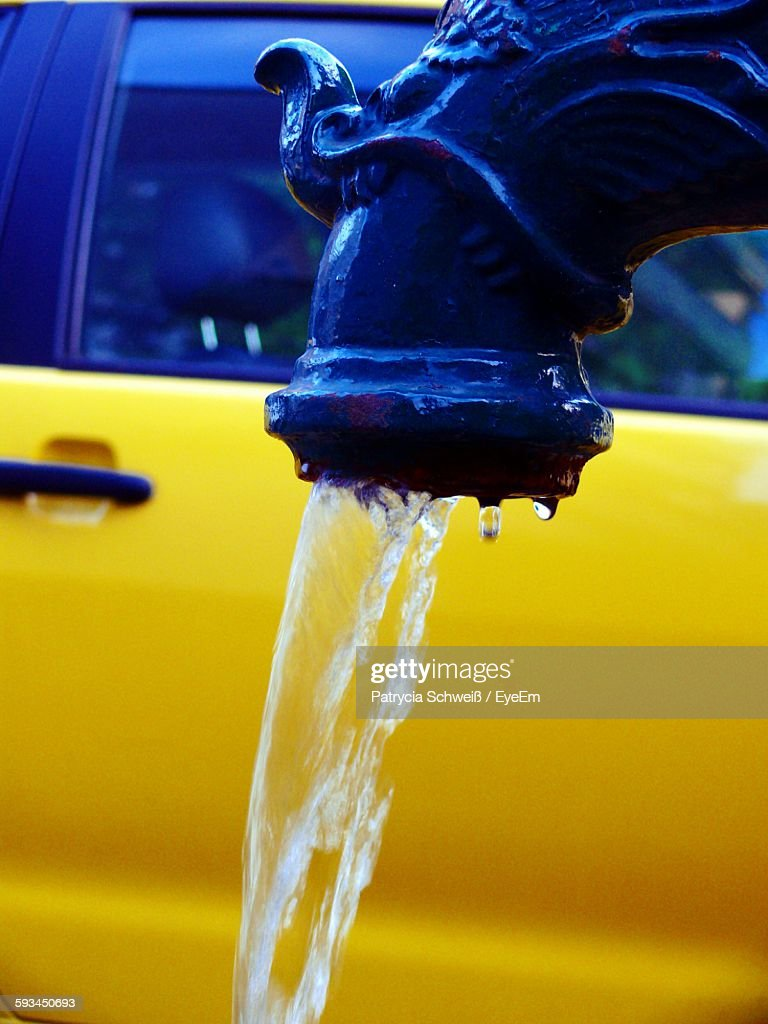 Closeup Of Water Falling From Faucet Against Yellow Car Stock ...