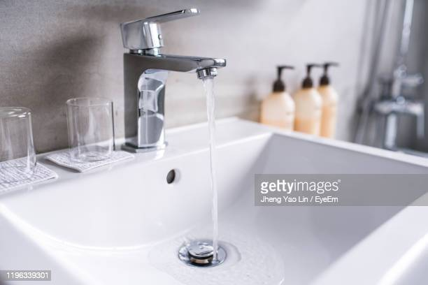 close-up of water falling from faucet in bathroom - 水周り ストックフォトと画像