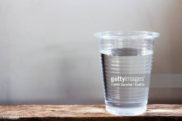 close-up of water in disposable cup on table - disposable cup stock pictures, royalty-free photos & images
