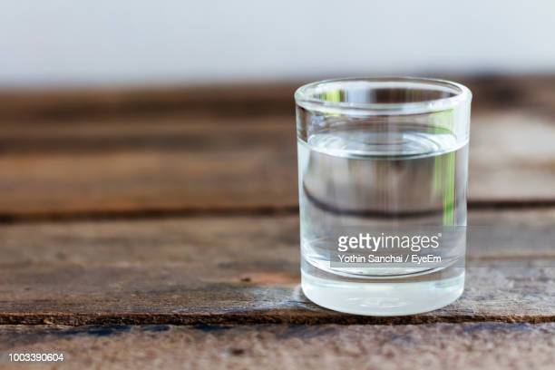 close-up of water in drinking glass on wooden table - glass of water stock pictures, royalty-free photos & images