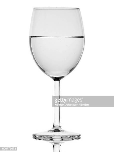 Close-Up Of Water In Wineglass Against White Background
