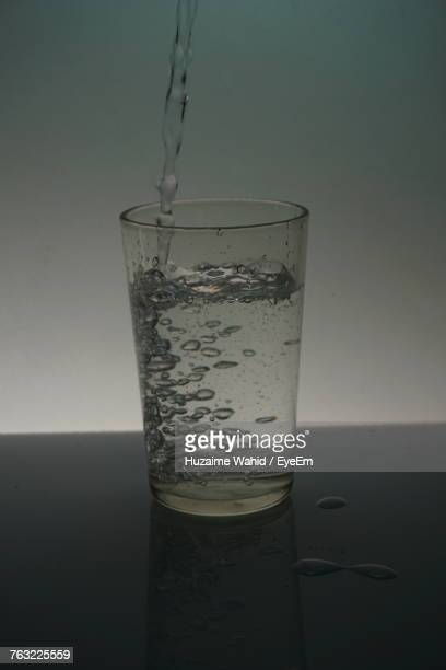 Close-Up Of Water Pouring In Glass On Table