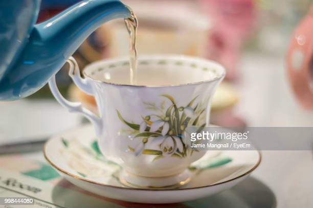 close-up of water pouring in tea cup on table - saucer stock pictures, royalty-free photos & images