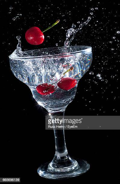 Close-Up Of Water Splashing From Glass With Cherry Into It