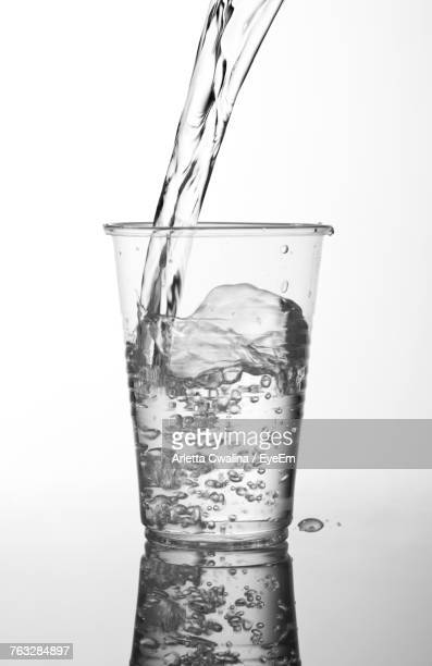 close-up of water splashing in drinking glass against white background - mineral water stock photos and pictures
