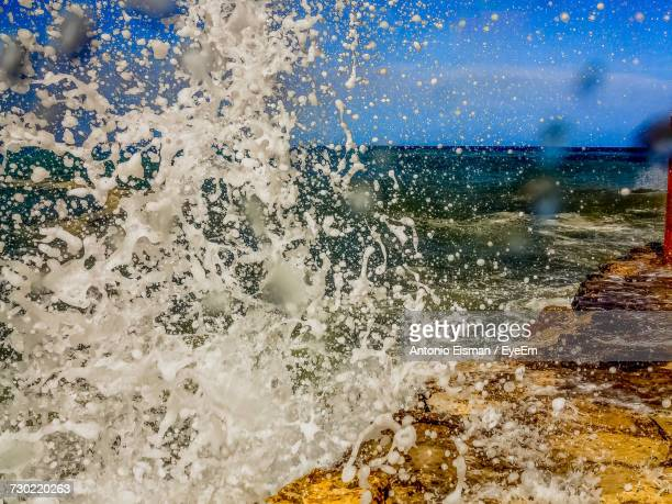 Close-Up Of Water Splashing In Sea Against Sky
