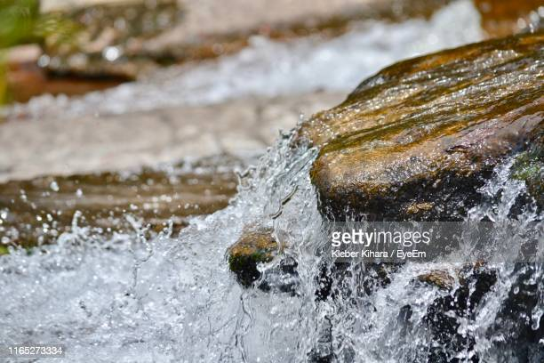 close-up of water splashing on rock - bach stock-fotos und bilder