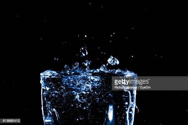 Close-Up Of Water Splashing Over Glass Against Black Background