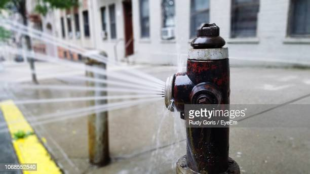 Close-Up Of Water Spraying From Fire Hydrant On Sidewalk