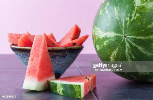 close-up of watermelon on table against purple background - watermelon stock pictures, royalty-free photos & images