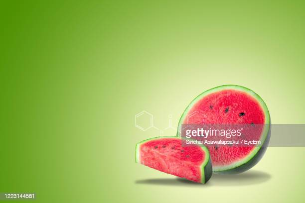 close-up of watermelon over green background - halved stock pictures, royalty-free photos & images