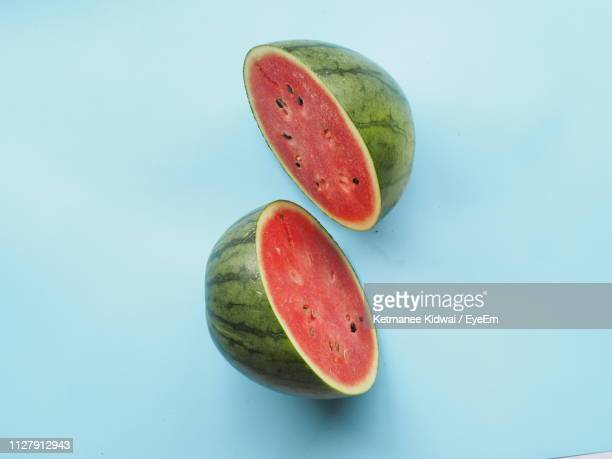 close-up of watermelon slices on blue background - watermelon stock pictures, royalty-free photos & images